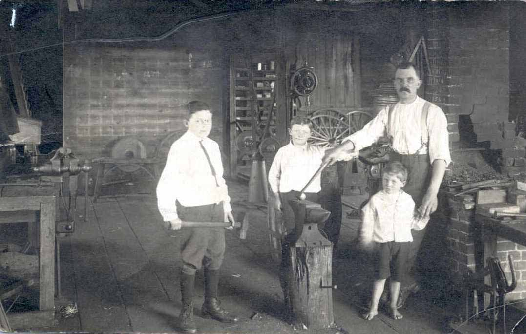 Jesse Higginbottom and his sons in his blacksmith shop